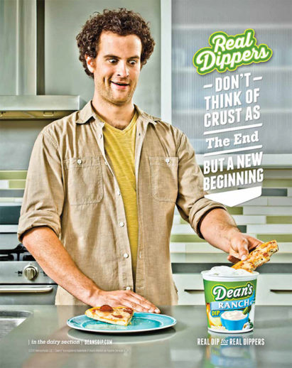 Photograph of man dipping a pizza crust into a tub of Dean's Dip