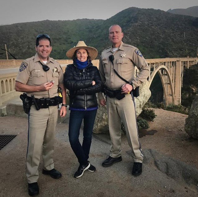 Photographer Lori Adamski-Peek takes a break with CHP troopers after a Highway 1-Bixby Bridge road closure for a shoot for New Balance Women.